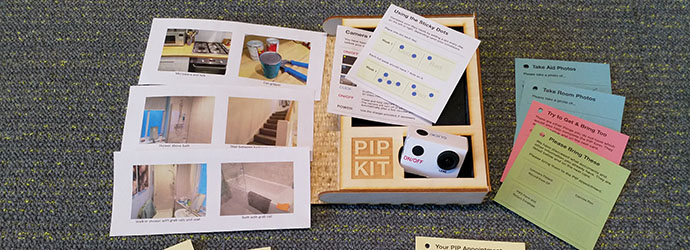 Photograph of the PIP Kit wooden enclosure box with materials laid out around it