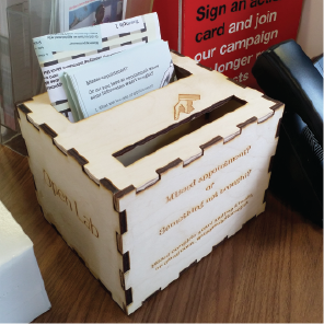 The actual response card holder and collector, laser cut from 6mm birch plywood, showing the box in place with cards ready to use and an instruction leaflet
